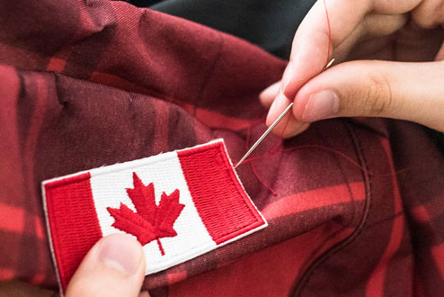 Sewing a Canadian flag onto clothing