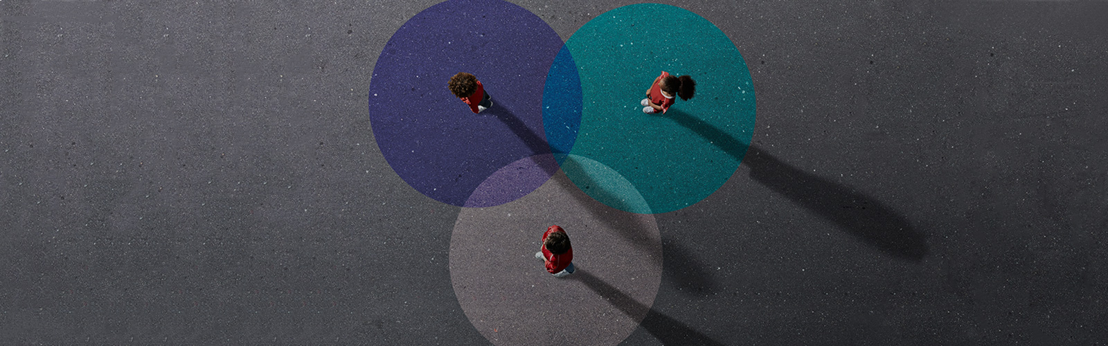 aerial view of 3 people standing in coloured circles on the ground
